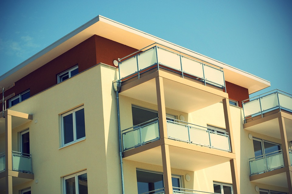 zdjęcie przedstawia mieszkanie w nowoczesnym budownictwie. Kadr obejmuje trzy kondygnacje patrząc od góry, wraz z balkonami. Fasada bloku jest koloru beżowego z ciemnoczerwonym dodatkiem
