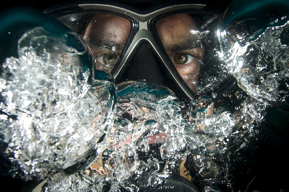 zdjęcie przedsawia ciasny kadr twarzy nurka, ma na sobie gogle i najprawdopodobniej butlę z gazem, ponieważ wokół niego jest spieniona woda. Patrzy prosto na nas