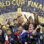 zdjęcie całej drużyny piłkarskiej Francji z trofeum, cieszącej się z wygranych Mistrzostw Świata