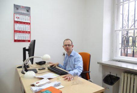 doktor Krzysztof Kurowski który udzielił wywiadu. Uśmiecha się do zdjęcia, siedzi przy biurku. Na blacie leż klawiatura i stoi monitor komputerowy, leżą różne papiery oraz książki,