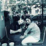 zdjęcie przedstawia dwoje młodych ludzi siedzących za witryna szklana kawiarni, patrzących w kadr i uśmiechających się do zdjęcia. Na szybie białym markerem napisane jest: Jesteście dobrzy, dziękujemy, dobra kawiarnia