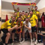 zdjęcie w szatni drużyny MKSN Mazowsze, po wygranym meczu. Trzymają swój szalik, oraz pozują do zdjęcia z wielką euforią