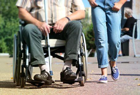 na zdjęciu znajduje się człowiek na wózku inwalidzkim, a za nim stoi kobieta. Zdjęcie jest tak skadrowane, że nie widać ich twarzy. Mężczyzna trzyma również kulę do podpierania podczas chodzenia.