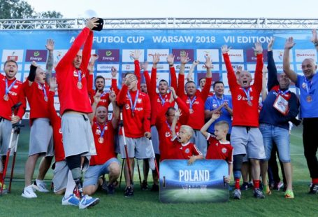 radość naszych ampfutbolistów po wygranym meczu. Wszyscy ubrani są w czerwone bluzy z długim rękawem, oraz białe szorty, większość z radości ma uniesione ręce w górze. Pozują na ściance sponsorów