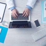 zdjęcie zrobione od góry, przedstawia dłonie lekarza spoczywające na klawiaturze od laptopa, obok leżą dokumenty, okulary, aparat do mierzenia ciśnienia, komórka, stoi szklanka z wodą oraz kubek z długopisami