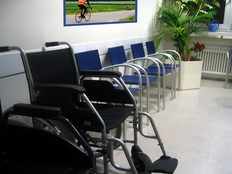 zdjęcie przedstawia poczekalnię do lekarza, stojące krzesła a wśród nich jeden wózek inwalidzki. Wszystkie siedzenia są puste, na ścianie wisi zdjęcie jadącego na rowerze kolarza