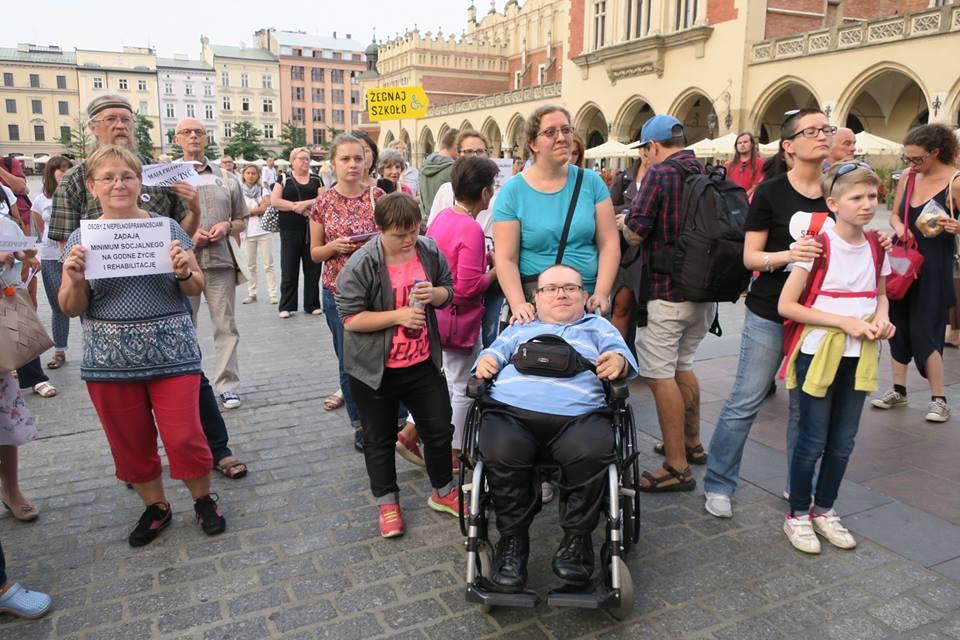 protest niepełnosprawnych z rodzinami odbywający się w Krakowie. W tle widoczne są sukiennice. Protestujący trzymają kartki z różnymi hasłami m.in. opieka to praca, lub bunt jest naszym obowiązkiem