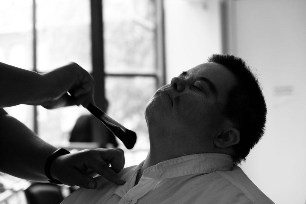 na zdjęciu mężczyzna z zespołem downa w trakcie przygotowań do spektaklu u wizażystki