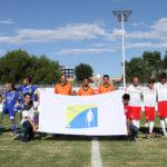 zdjęcie przedstawia dwie grupy ampfutbolistów Polski oraz Japonii, pozujące do wspólnego zdjęcia przed meczem, Japończycy obrani na niebiesko stoją po lewej stronie, w środku sędziowie w pomarańczowych koszulkach, a po prawej stronie Polacy w biało czerwonych strojach