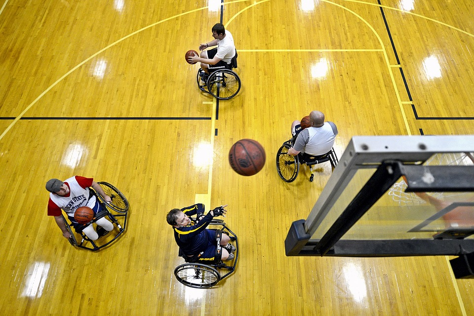 zawodnicy na wózkach w trakcie gry w koszykówkę. Zdjęcie wykonane od góry, z perspektywy wiszącego nas zawodnikami kosza. Na zdjęciu znajduje się czterech sportowców
