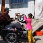 dziewczynka z niepełnosprawnym ojcem przed domem, ojciec siedzi na wózku, dziewczynka stoi przed nim i pomaga mu