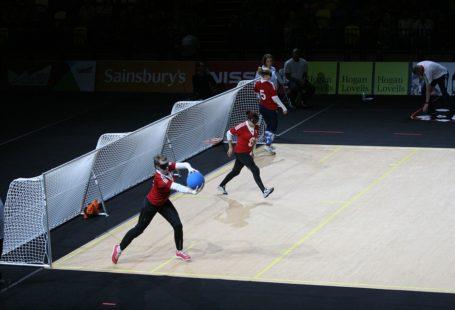 Mecz kobiet w goalballu, przy bramce stoją trzy kobiety z zasłoniętymi oczami, jedna z nich trzyma piłkę. Mecz rozgrywa się na hali. Kobiet ubrane są w czarne getry oraz biało czerwone koszulki.