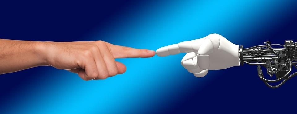 zetknięta palcem wskazującym ręka ludzka z ręką robota
