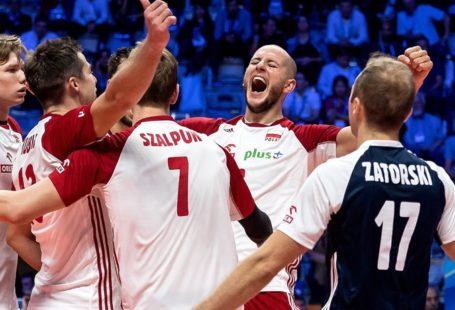 szczęśliwi siatkarze po wygranym meczu, na zdjęciu widoczny jest Bartosz Kurek oraz reszta drużyny obrócona tyłem
