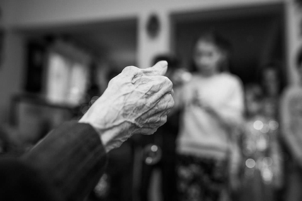 Zdjęcie czarno białe, na pierwszym planie widoczna jest wyostrzona dłoń strszej osoby, jest chuda i wyniszczona, z widocznymi zyłami i przebarwieniami. W tle widoczne są inne osoby, niewyraźne i rozmazane
