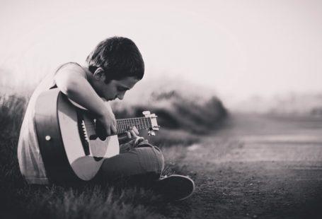 zdjęcie w melancholijnym i spokojnym klimacie, w odcieniach szarości, młody chłopak siedzi na trawie i gra na gitarze. siedzi po turecku bokiem do fotografa, jest skupiony na grze
