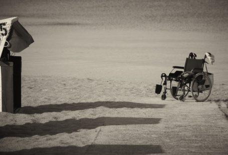 zdjęcie przedstawia wózek inwalidzki samotnie stojący na plaży. Obok stoi kosz, w którym można siąść. Zdjęcie w odcieniach szarości, jest nostalgiczne i daje wiele do myślenia.