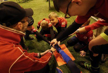 Szczęśliwi chłopcy stojący w kole po meczu. Zdjęcie wykonane z góry w trakcie wspólnego przybijania piątek z trenerami