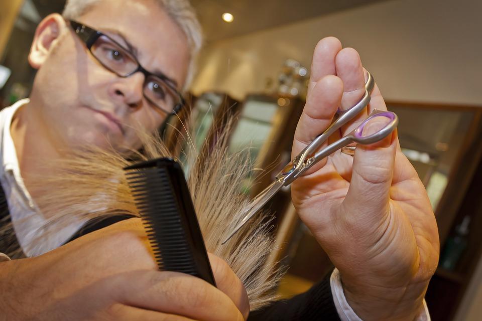 zdjęcie przedstawia zbliżenie na twarz fryzjera i jego dłonie podczas obcinania włosów, w których trzyma nożyczki i grzebień. Jego mina wskazuje na to, że jest bardzo skupiony podczas wykonywanej czynności