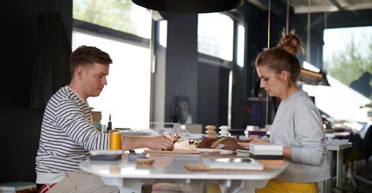 Kadr z programu Szybki Dom. Nasi architekci siedza przy stole i projektują. Wnętrze, w którym siedzą jest nowoczesne