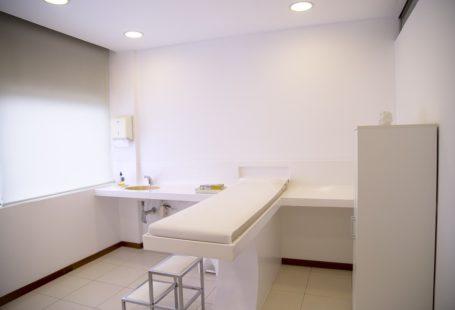 zdjęcie przedstawia gabinet lekarski, widoczne jest łóżko oraz jasne ściany