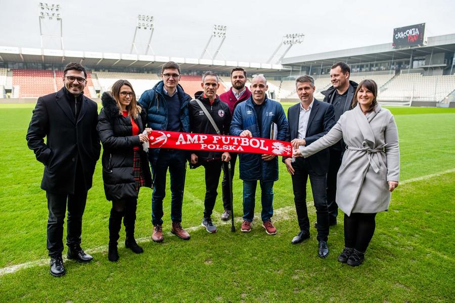 Wizytacja EAFF w Krakowie. Cała delegacja stoi na środku murawy na stadionie trzymając szalik AMP FUTBOL