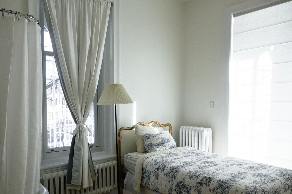 sypialnia w jasnych barwach. Łóżko jednoosobowe obok lampka
