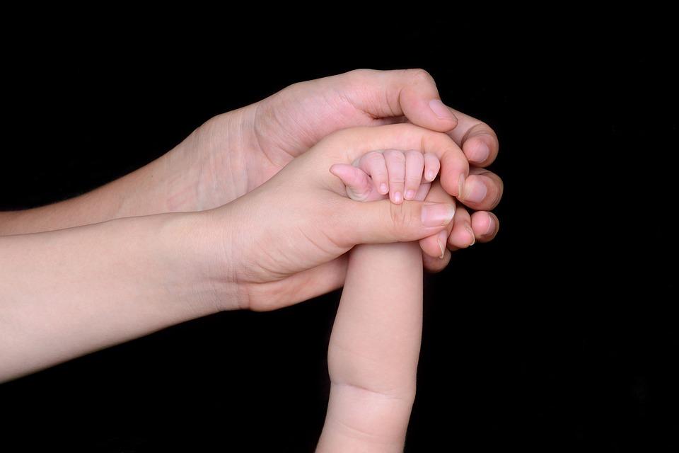 zdjęcie przedstawia trzy złączone w jednym uścisku dłonie, ojca matki oraz dziecka