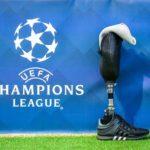 Plakat, na którym na niebieskim tle znajduje się logo UEFA CHAMPIONS LEAGUE, a obok na murawie stoi proteza w adidasie