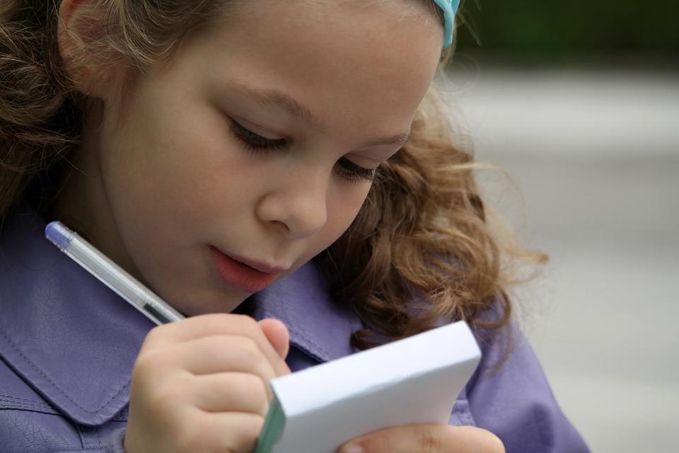 dziewczynka około ośmiu lat ucząca się pisać