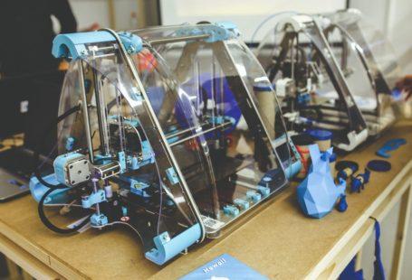 Zdjęcie przedstawia przykładowa drukarkę 3D, jest wielokolorowa, z dużą ilością guzików i kabli