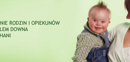 banner ze strony internetowej stowarzyszenia rodzin i opiekunów osób z zespołem downa bardziej kochani, przedstawia matkę trzymającą na rękach niemowlaka z zespołem downa, oboje są bardzo uśmiechnięci