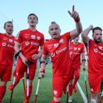 Zdjęcie przedstawia polskich piłkarzy ampfutbolowych, radosnych po wygranej z Włochami. Ubrani są w czerwone stroje