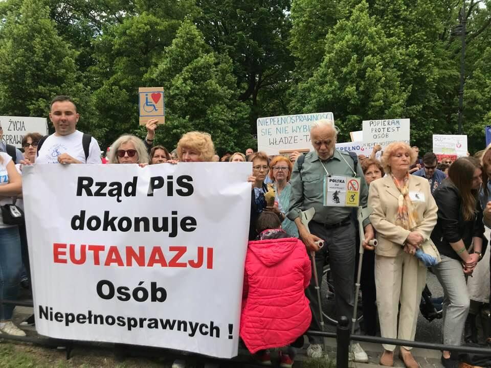 Ludzie protestujący pod kancelaria premiera. Trzymają w rękach transparenty z napisami: Rząd PIS dokonuje eutanazji osób niepełnosprawnych, niepełnosprawności się nie wybiera - władze tak, popieram protest osób niepełnosprawnych, itp