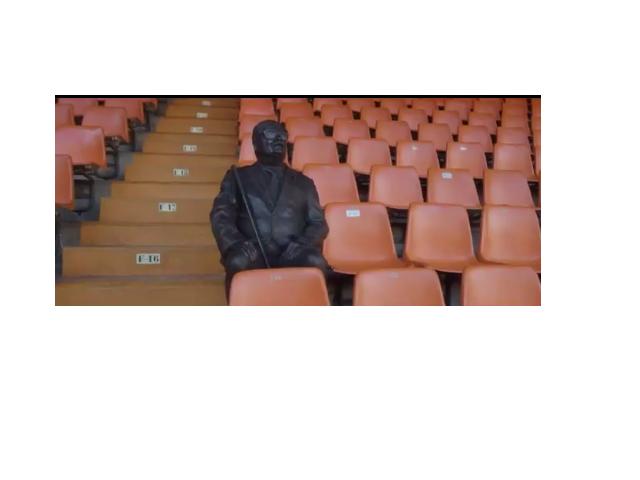 Zdjęcie przedstawia pomnik niewidomego kibica siedzącego na jednym z krzesełek na stadionie.