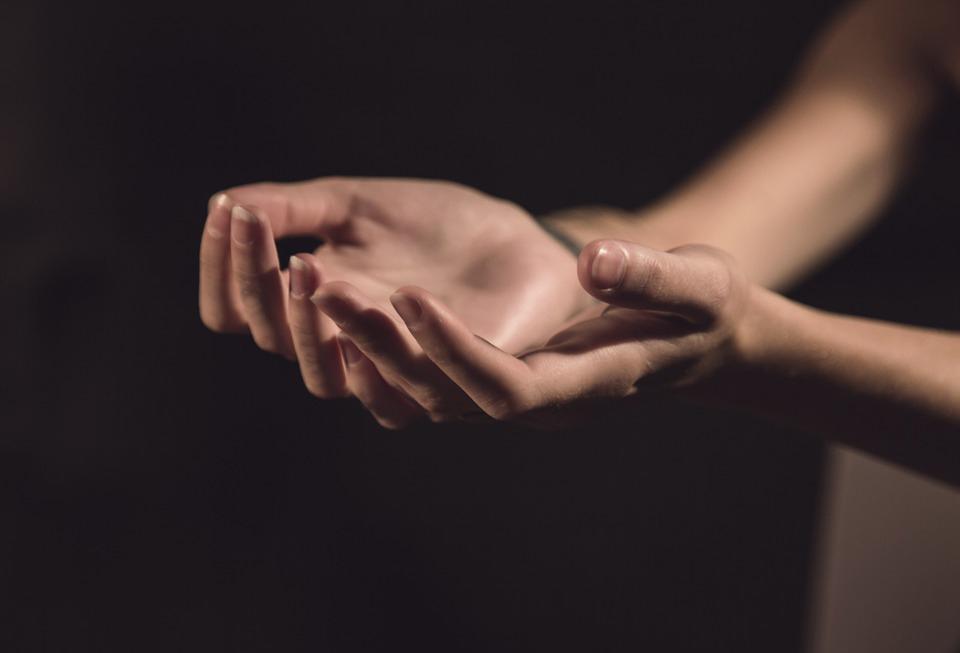 zdjęcie przedstawia dwie dłonie - prawdopodobnie kobiece - na ciemnym tle