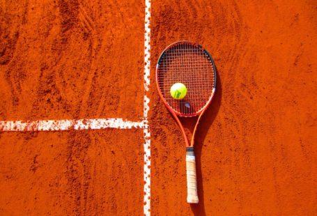 na zdjęciu widoczna jest rakieta do tenisa, na której leży piłeczka tenisowa. Tłem jest kawałek kortu tenisowego, czyli pomaranczowe podłoże z namalowanymi białymi liniami,ponieważ zdjęcie zrobione jest z perspektywy lotu ptaka.