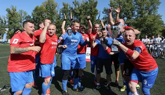 radość zawodników po wygranej. Wszyscy stoją w okręgu i wymachują rękoma w stronę aparatu