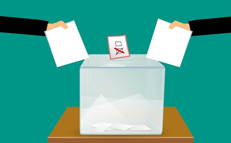 rysunek przedstawiający urnę do wrzucania kart wyborczych oraz rękę trzymająca wypełnioną kartę