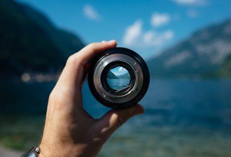 zdjęcie przedstawia obiektyw trzymany w dłoni mężczyzny na tle pięknego krajobrazu morsko-górskiego