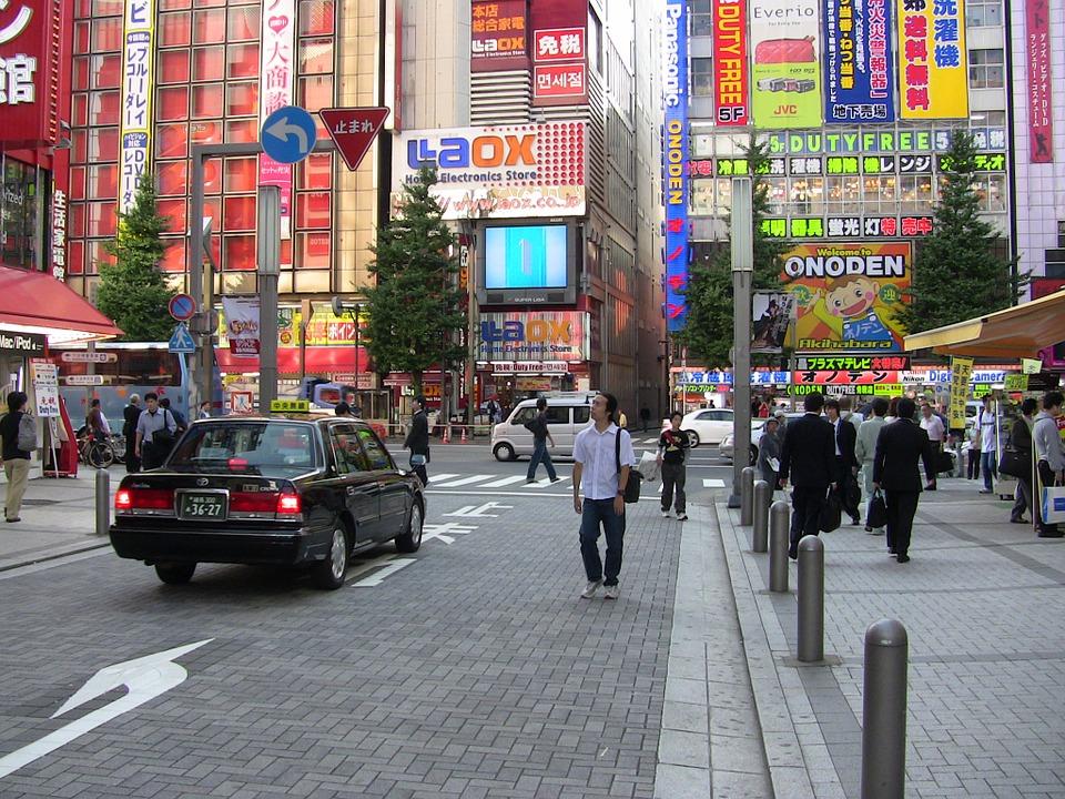 zdjęcie miejskie ulicy w Tokio. Widać spacerujących ludzi oraz w tle wysokie kolorowe wieżowce pełne reklam
