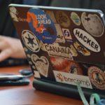 zdjęcie przedstawia osobę - a dokładnie dłoń osoby korzystającą z laptopa, na którym ponaklejane są różne naklejki, a wśród nich jedna ze słowem hacker