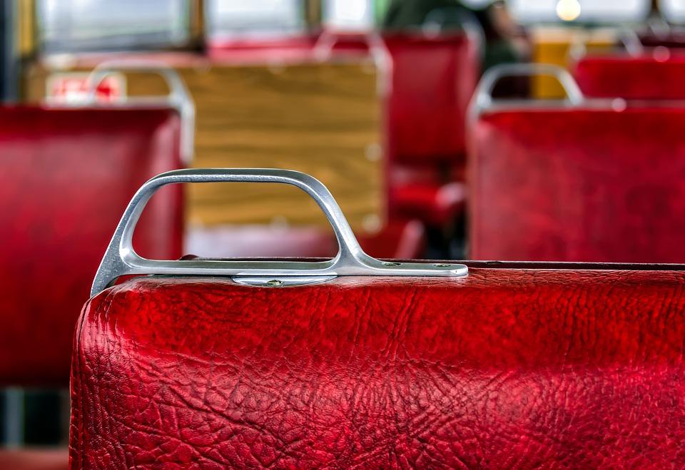 wnętrze starego bezprzedziałowego wagonu pociągowego. Siedzenia są obite grubą czerwoną