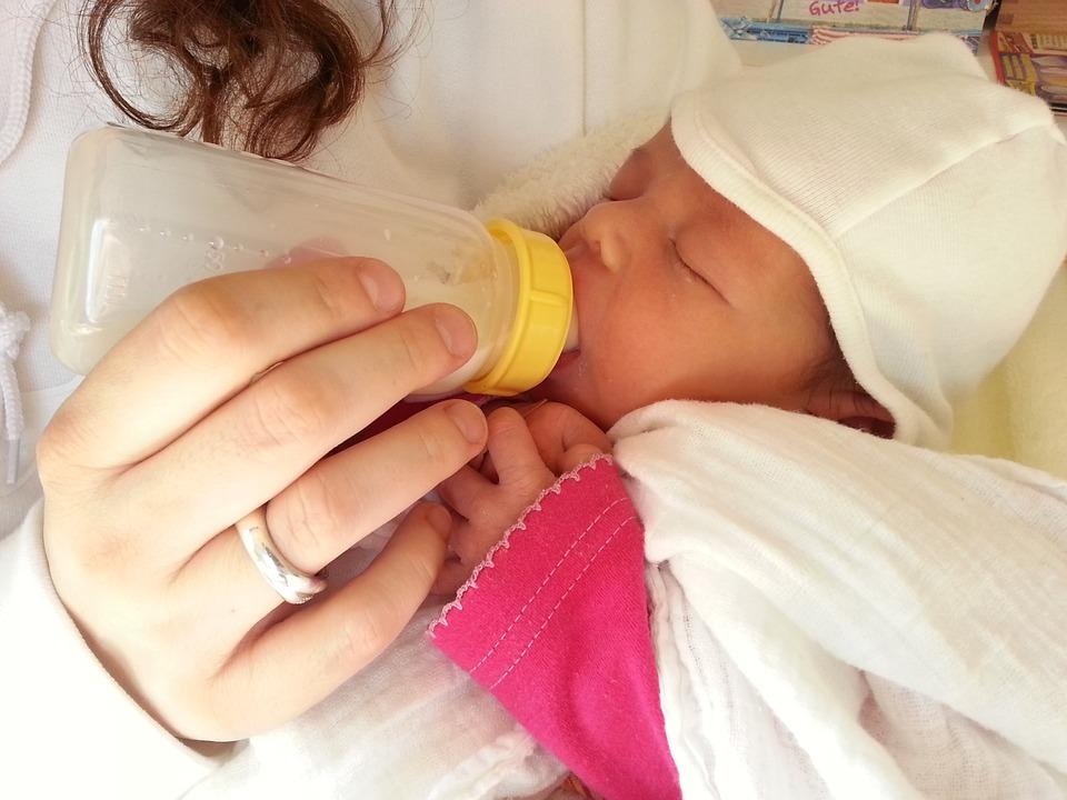 noworodek pijący mleko z butelki, trzymany przez matkę.