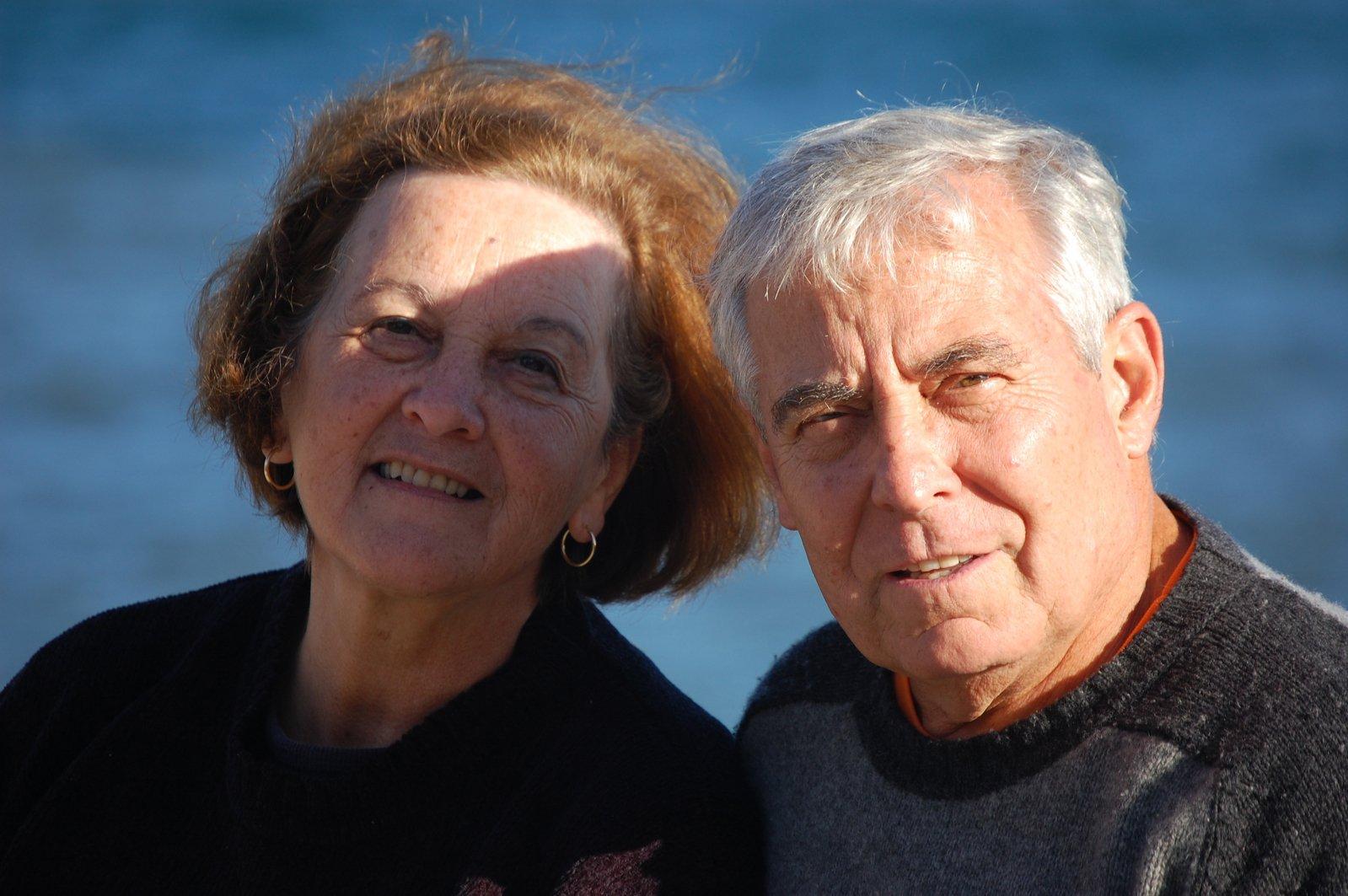 old-couple, portret na tle akwenu wodnego dwóch osób starszych, mężczyzny i kobiety. wpatrzeni są w obiektyw, uśmiechają się oraz mrużą oczy przez padające światło słoneczne