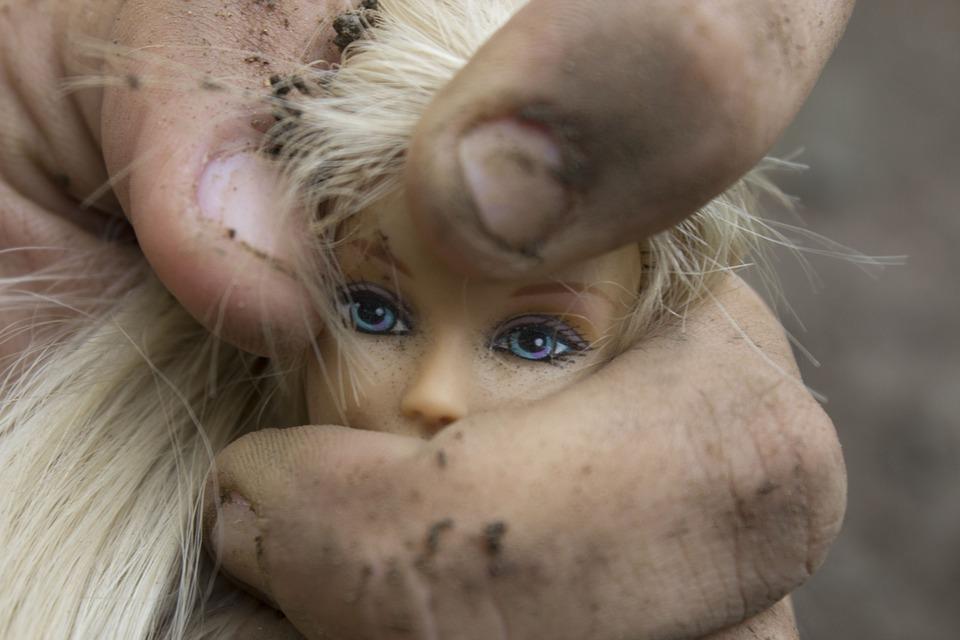kadr na brudną rękę małego dziecka trzymającą głowę lalki barbie, zdjęcie sugeruje przemoc, opresję, ucisk