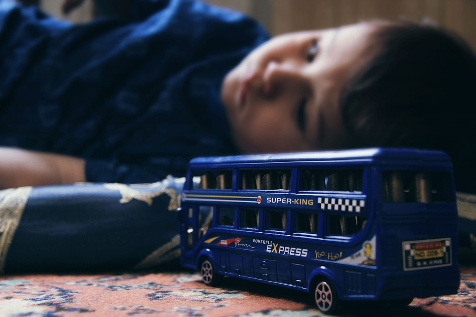 na zdjęciu znajduje się smutne dziecko. Leży na podłodze i patrzy na nieokreślony punkt. Jest na drugim planie, dlatego jego sylwetka jest lekko rozmazana i niewyraźna