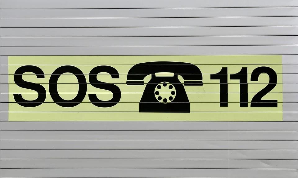 zdjęcie przedstawia napis sos z ikonka telefonu i numerem 112, na tle z jasnych desek